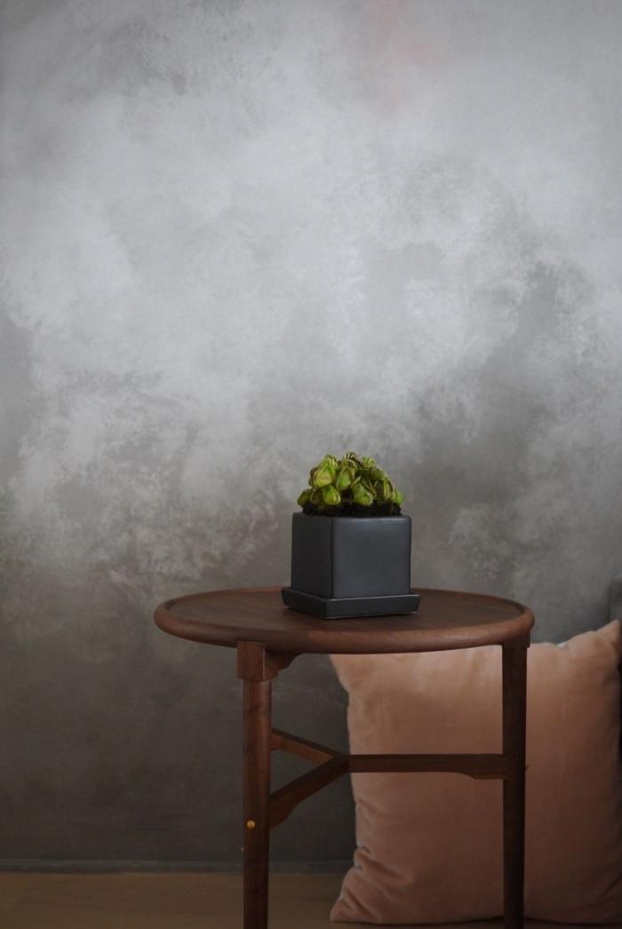 revêtement mural tendance à texture béton, décoration salon aux murs gris béton avec table café bois marron
