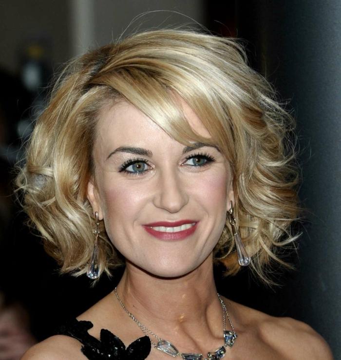 carré bouclé plongenat avec frange de biais, cheveux blonds, coloration ton sur ton, coupe de cheveux courte pour femme de 50 ans