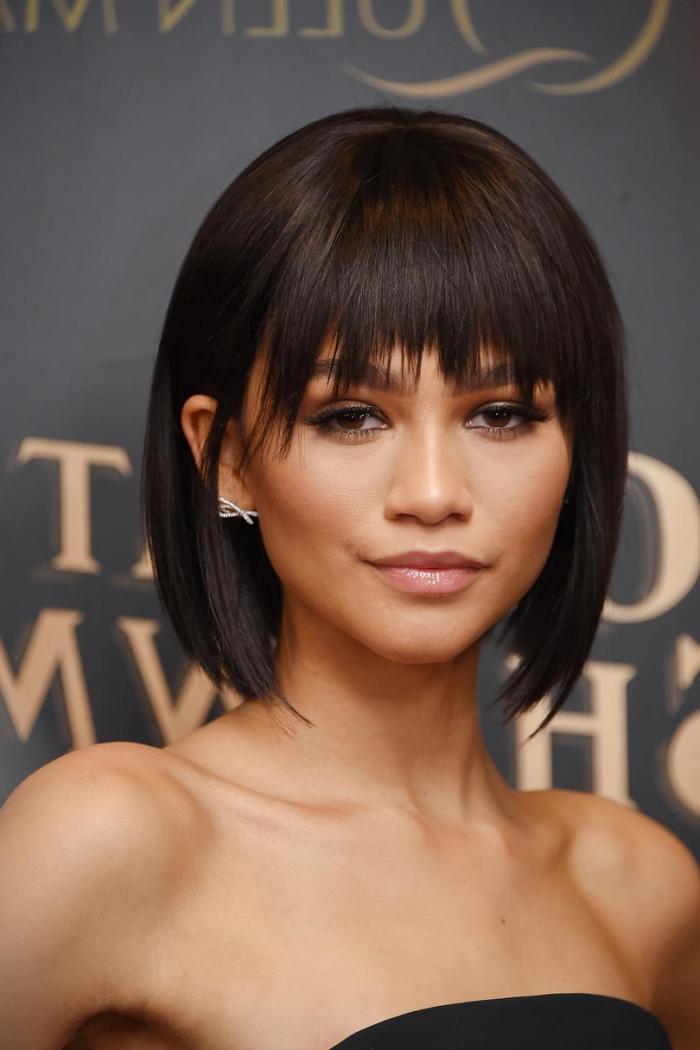 coiffure avec frange de célébrité de Zendaya, idée maquillage pour yeux marron avec eye liner et fards à paupières marron, exemple lissage permanent
