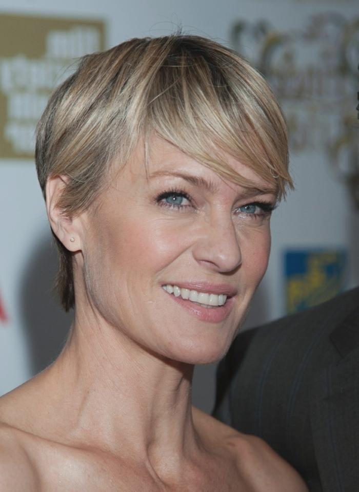 femme blonde aux cheveux fins avec coupe pixie, frange de côté, maquillage discret