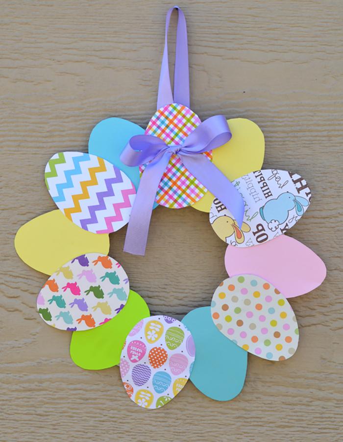 bricolage de pâques en maternelle, couronne de paques en oeufs de carton coloré à suspendre sur un ruban violet, deco de paques originale bricolage enfant