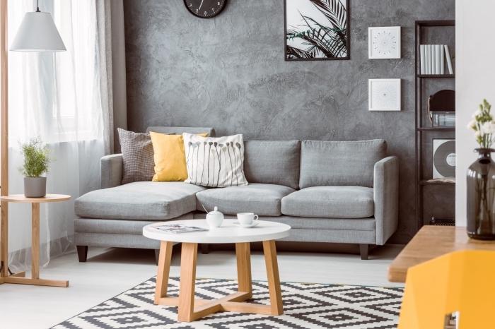 aménagement salon minimaliste aux murs à texture béton avec meubles bois et canapé d'angle gris, modèle tapis scandinave blanc et noir