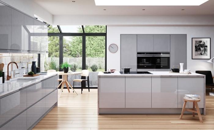 design contemporain dans une cuisine blanche au plancher bois aménagée avec meubles en blanc et gris laqué