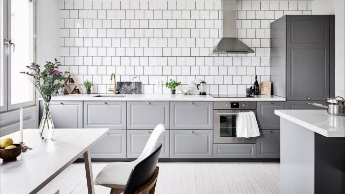 déco de cuisine traditionnelle avec revêtement mural en carreaux blancs et plancher bois blanc, exemples meubles haut cuisine en gris