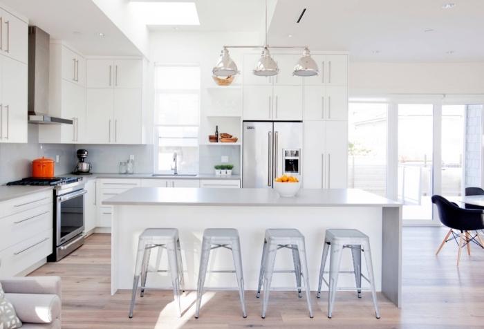 exemple de cuisine grise et blanche, déco de cuisine en l avec îlot, pièce au plancher bois et murs blancs avec meubles gris clair