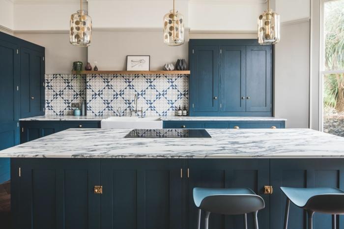 cuisine élégante avec un îlot, tabourets de bar, lampes suspendues, carrelage mural géométrique, armoires bleues