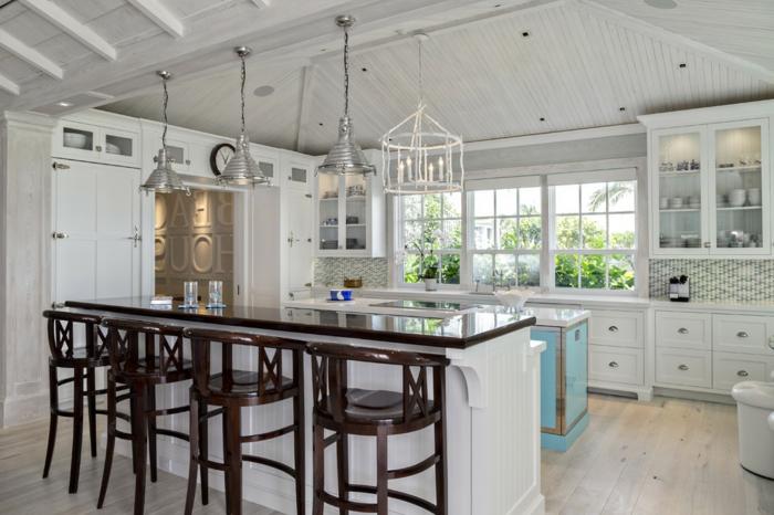 îlot de cuisine, chaises en bois foncé, lampes chromées pendantes, sol en bois, chandelier blanc