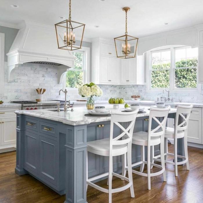 aménagement cuisine ancienne, îlot avec lavabo élégant, chaises rétro blanches, chandelier lanter,