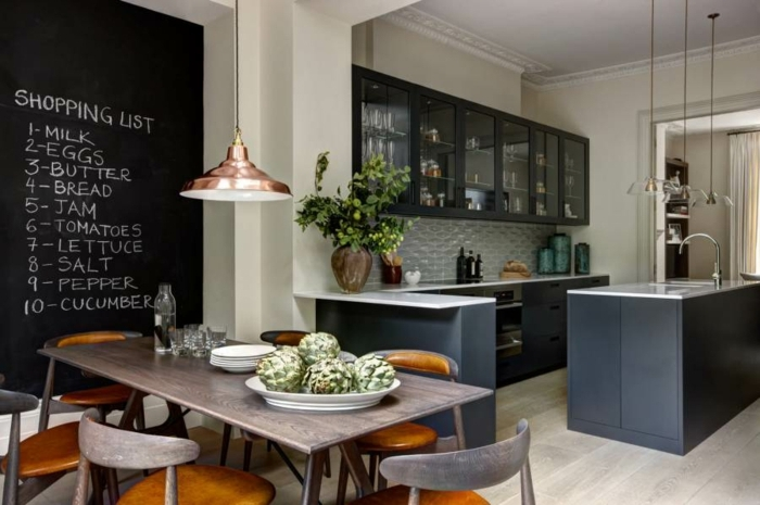 ardoise murale cuisine, table longue en bois, chaises de bois bicolores, armoires montées vitrées, îlot en noir et blanc
