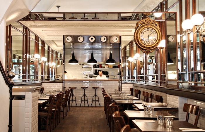 grand bistrot français, décor industriel, tables en bois avec chaises vintage, carreaux métro blancs, sol bois foncé