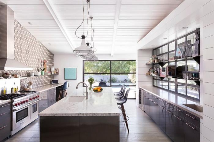grand îlot en marbre, meubles contemporains, suspensions cages industrielles, plafond lattes blanches