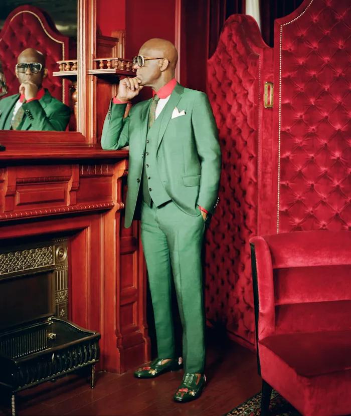 Dapper Dan dans un costume vert sur fond de velours rouge pour collaboration Gucci