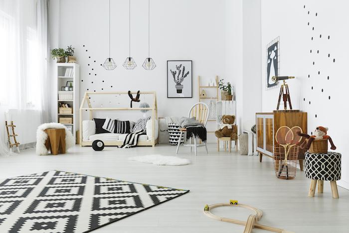 exemple amenagemet chambre montessori scandinave en noir et blanc et mobilier enfant en bois, parquet bois clair, tapis noir et blanc, echelle decorative, commode basse