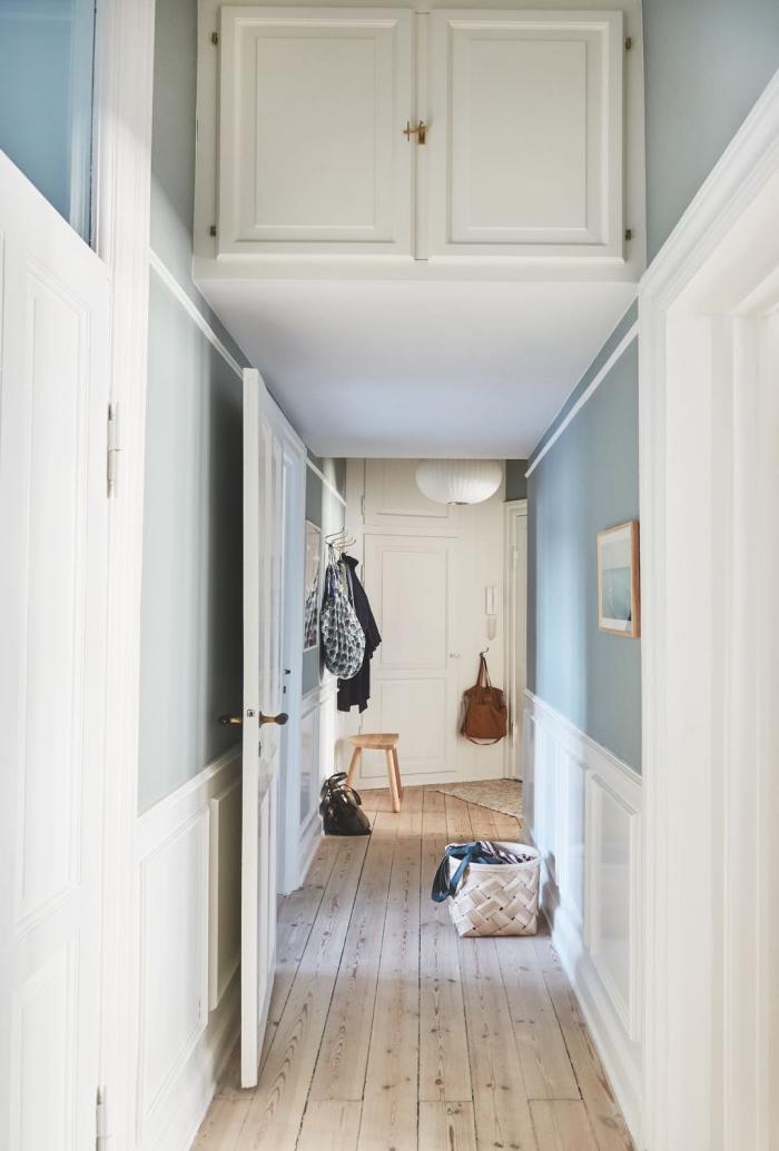 un couloir long et étroit de style scandinave avec un soubassement en moulure murale blanche et des murs peints en bleu gris clair