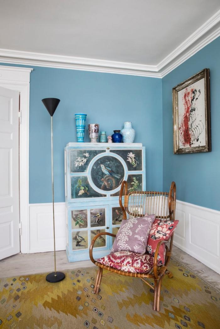 salon de style éclectique avec des murs couleur bleu sarcelle mis en valeur par une moulure murale blanche