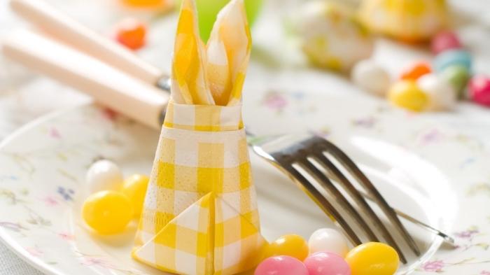 comment plier des serviettes en papier pour décorer une table de pâques, serviette à carreaux jaune et blanc pliée en lièvre de pâques