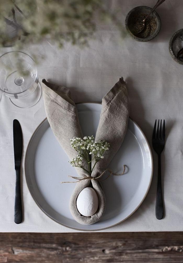 une belle table de pâques naturelle de style rustique, serviette en lin en forme de lapin paques
