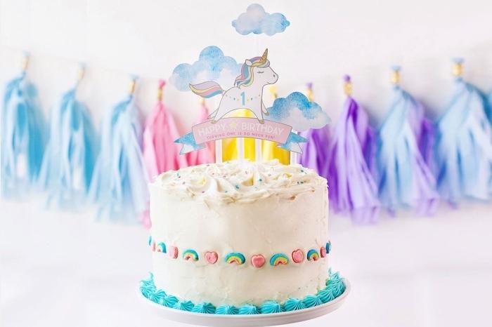 idée de gateau anniversaire enfant 1 an sur le thème licorne, gâteau au glaçage blanc décoré de bonbons arc-en-ciel et d'un cake-topper licorne