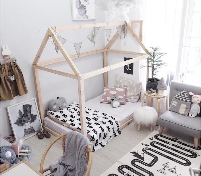 lit cabane montessori en bois sur parquet bois clair, fauteuil gris clair bas, mobilier bois nordique, jouets scandinaves