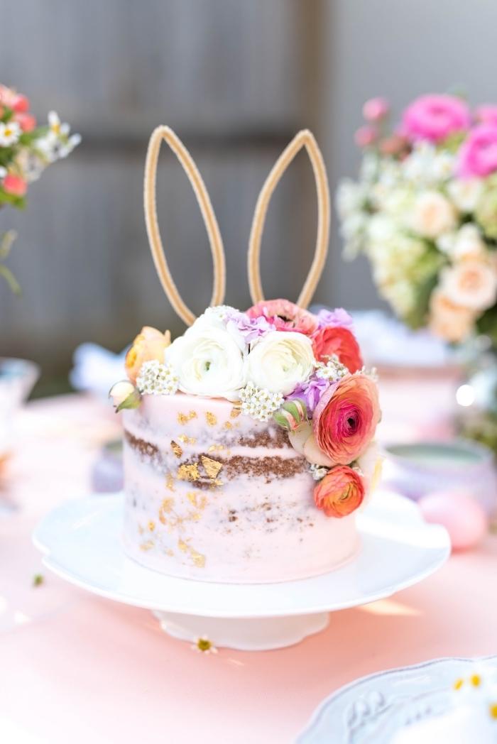 joli naked cake recouvert d'une couche légère de crème au beurre rose et décoré de fleurs, cake topper oreilles de lapin