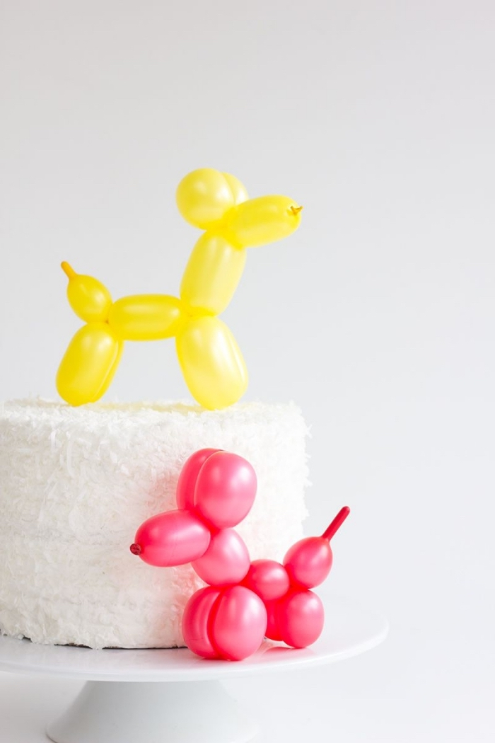 gateau anniversaire enfant au glaçage de crème beurre et noix de coco décoré avec deux petites sculptures sur ballons