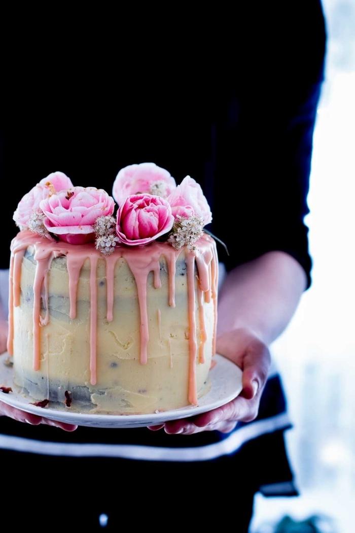 image gateau anniversaire sur le thème champêtre au glaçage coulant rose décoré de fleurs naturelles
