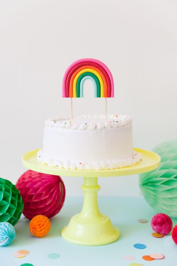 gateau anniversaire simple et beau au glaçage lisse de crème beurre orné d'un topper arc-en-ciel en pâte à modeler et posé sur un présentoir jaune citron