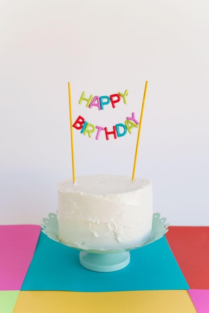 un cake topper joyeux anniversaire haut en couleur qui orne un gâteau d'anniversaire simple au glaçage de crème beurre