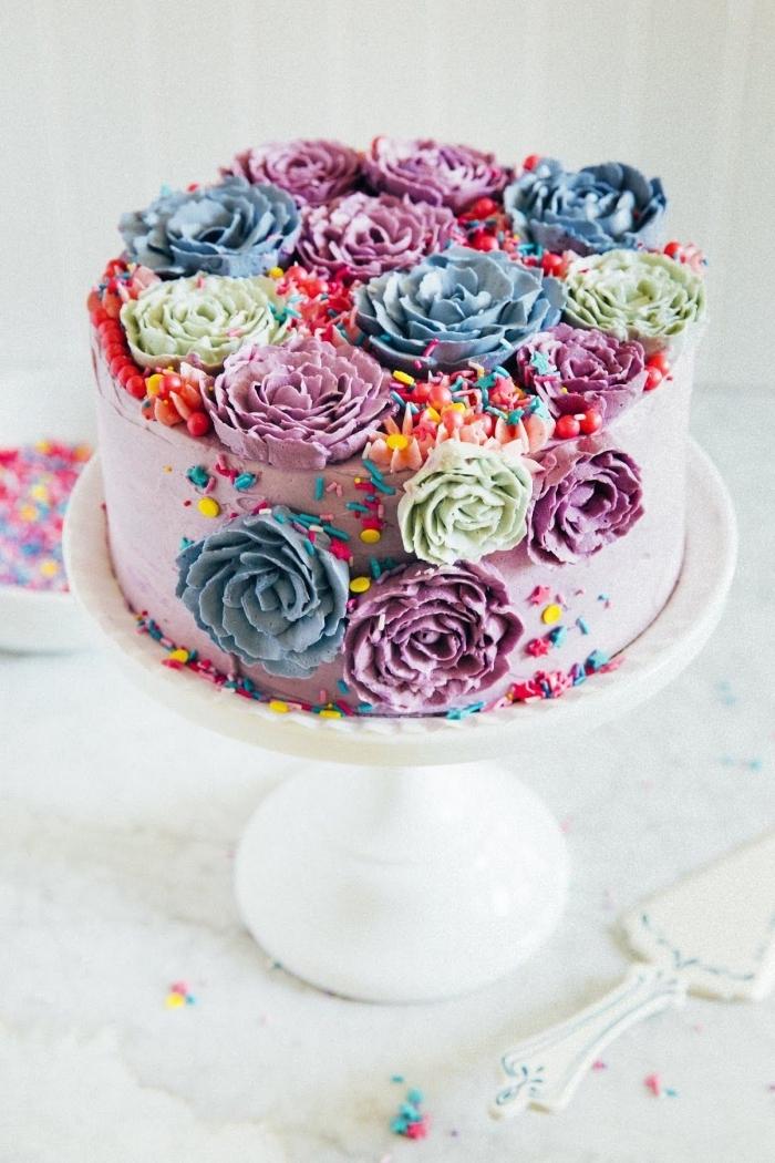 gateau anniversaire fille au glaçage rose décoré de petites fleurs lotus colorées en pâte d'amande et de vermicelles en sucre