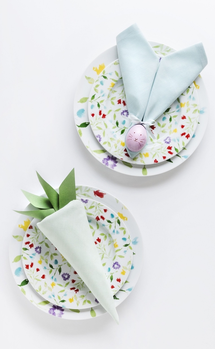modèle de pliage serviette simple autour d'un oeuf dans une assiette à motifs floraux, pliage d'une serviette en forme de carotte