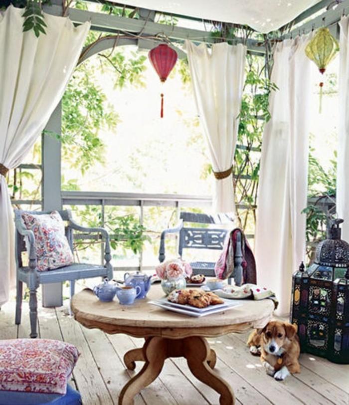 table basse bois brut et chaises bleues sur une terrasse bois brut, pergola à voiles blanches, deco exterieur style shabby chic