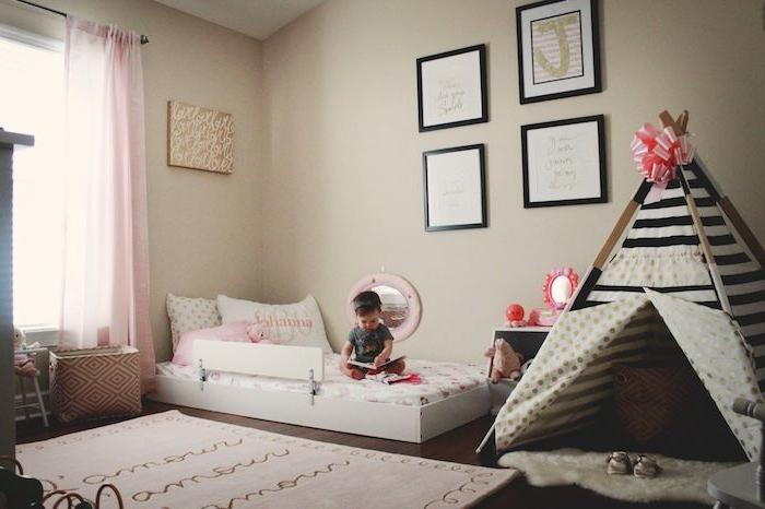idee deco chambre bebe fille selon la méthode montessori avec murs beiges, tipi fille en noir et blanc avec ruban en top, lit au sol blanc, cadres decoratifs