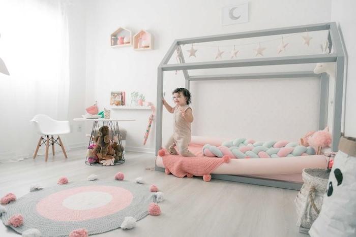 exemple de lit montessori cabane grise avec matelas rose, tapis de jeu rond gris et rose, parquet clair, table et chaise basse, etageres interessantes