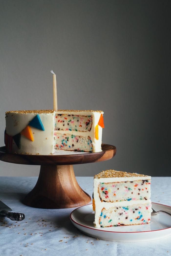 un gateau anniversaire enfant confettis en sucre décoré avec une guirlande fanions réalisée en pâte à sucre, décor en pâte à sucre à réalisé soi-même