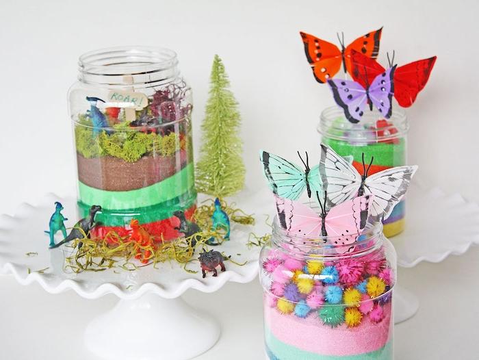 diy terrarium a faire soi meem dans un bocal en verre avec sable coloré pompons colorés, végétation artificielle et papillons de papier
