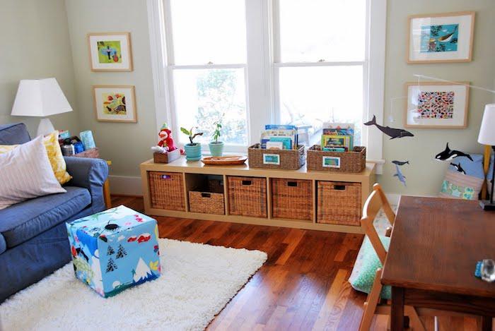 etagere basse bois avec rangement en paniers à jouets, parquet marron, tapis blanc, canapé bleu, matelas d activité au sol, coin montessori dans le salon