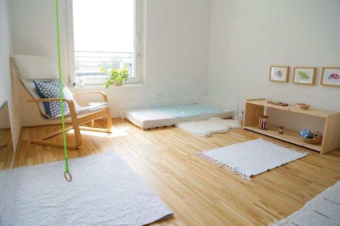 chambre sobre et épurée pour une ambiance montessori, parquet bois clair, tapis d'activité, matelas blanc, etagere bois rangement