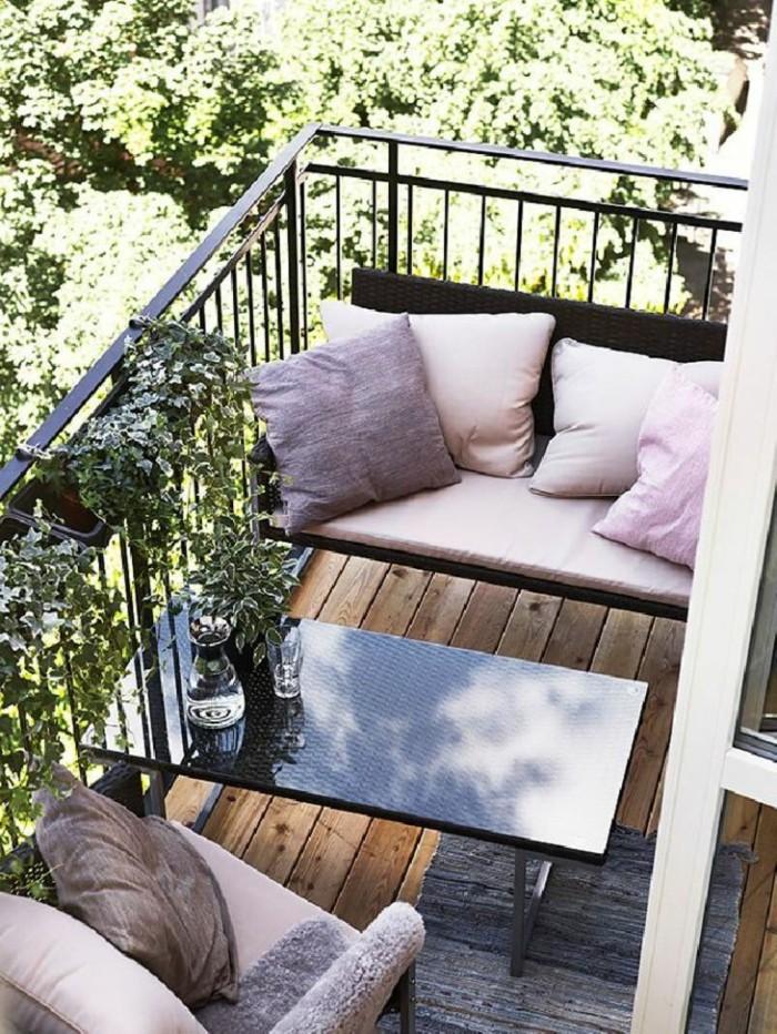 terrasse avec gradre corps noir, bancs metalliques noires, table basse noire, coussins decoratifs rose, tapis gris, deco de plates vertes