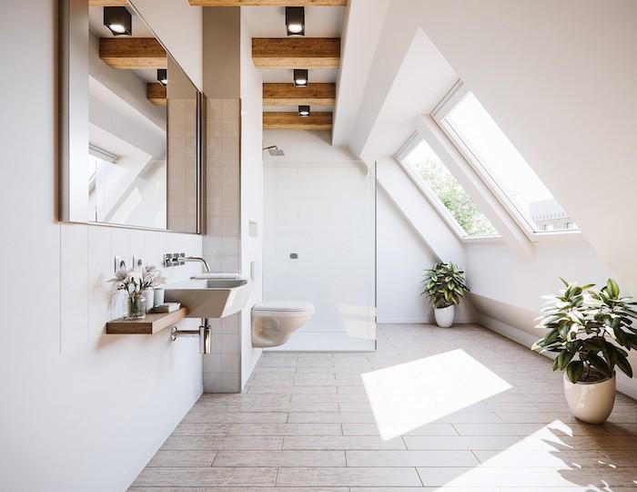 exemple de salle de bain mansardée à des éléments poutres apparentes, grand miroir horizontal, carrelage gris clair, wc suspendu, plantes en pots blancs, douche paroi vitré