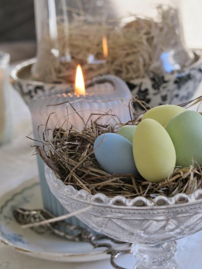 décoration de paques à fabriquer en oeufs teintes pâles, bougies allumées, nid de paques decoration