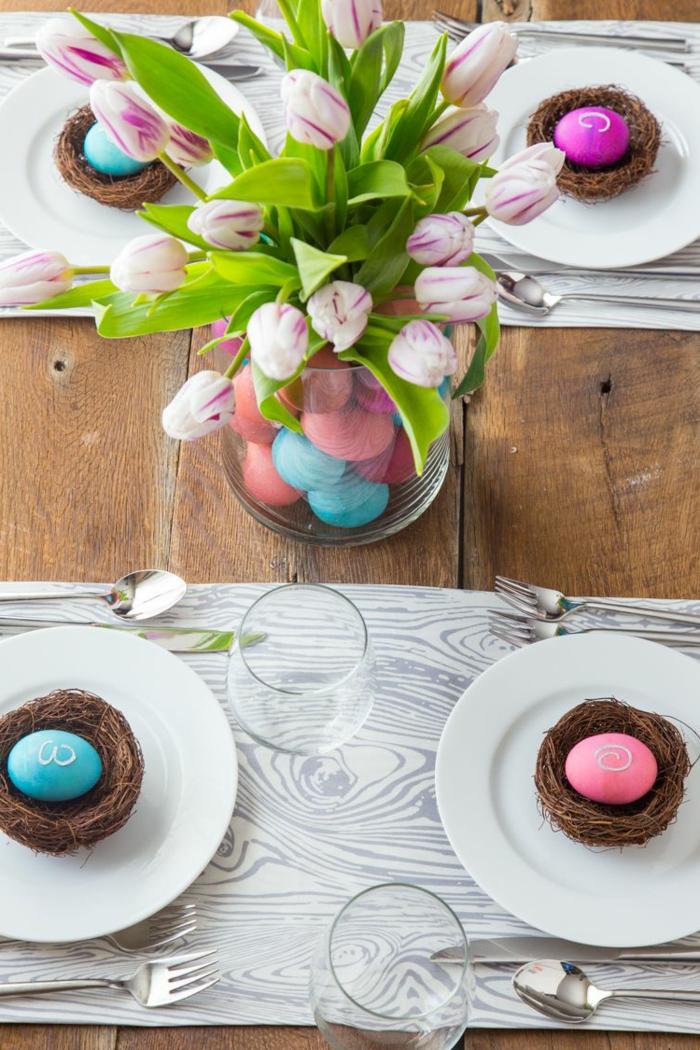 activité de paques, vase en verre avec tulipes lilas, remplie d'oeufs et nids avec des oeufs teintés, table en bois