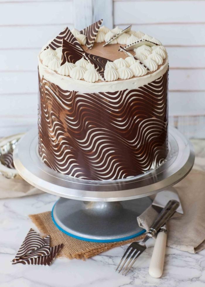 joli décor en chocolat qui entoure un gâteau d'anniversaire étagé, réalisé avec du chocolat fondu et une feuille transparente