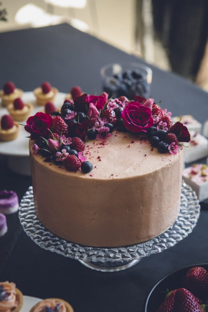 gateau anniversaire simple et beau au glaçage chocolat lisse sublimé par un joli décor de fleurs et de fruits rouges