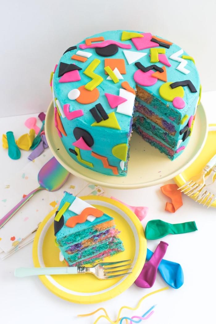 gâteau multicolore au glaçage bleu turquoise avec une deco pate a sucre abstraite de formes géométriques colorées