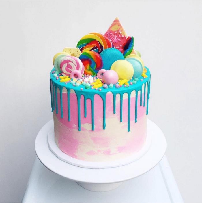gâteau d'anniversaire au glaçage coulant bleu décoré de toutes sortes de bonbons, soucoupes acidulées, sucettes et perles en sucre