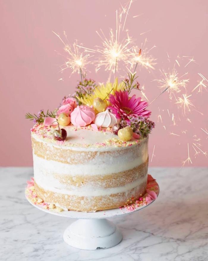 décoration de gâteau festive de meringues croquantes, de fleurs et de bougies feux d'artifice, gateau anniversaire simple et beau