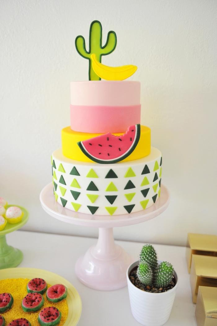 gâteau d'anniversaire étagé recouvert de pâte à sucre multicolore orné de petites décorations à motifs tropicaux