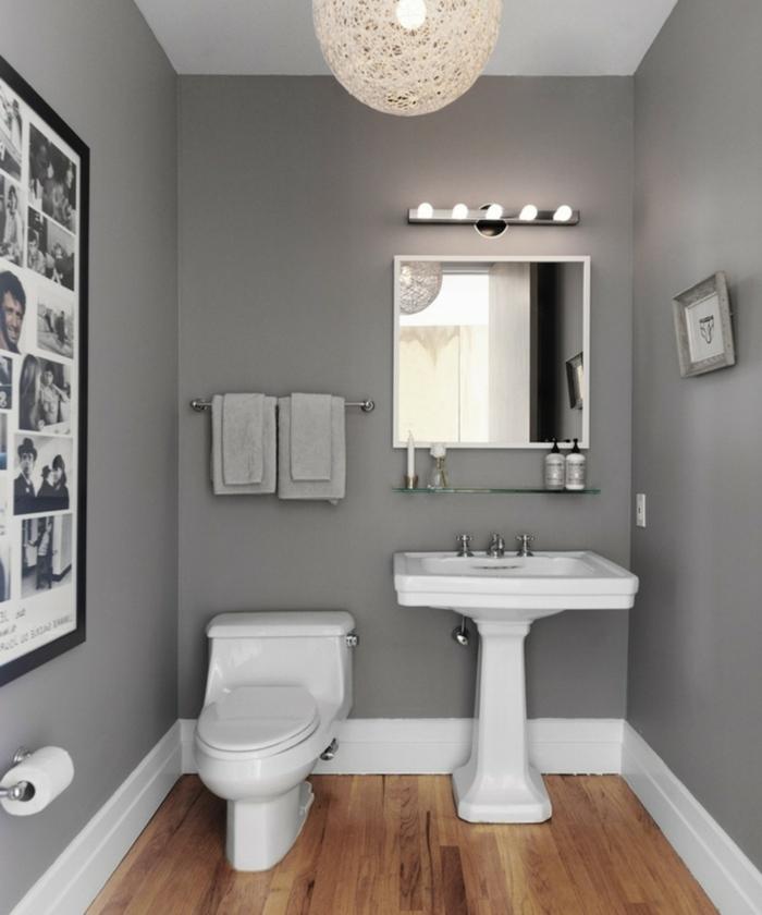 amenagement wc gris et blanc, sol en bois, grand luminaire, miroir ancadré, étagère en verre, photos monochromes