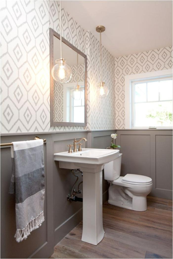 wc design en gris et blanc, vasque pied, sol en bois, lampes pendantes, papier peint géométrique, soubassement gris