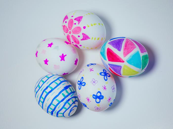 dessin aux feutres sur la surface d oeufs blancs à motifs triangles colorés, étoiles, fleurs et autres dessins colorés